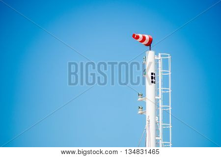 Frayed windsock in moderate wind against blue sky with few clouds