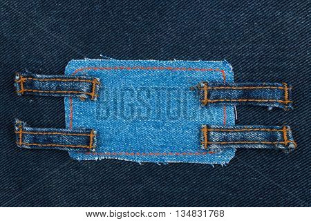 Frame made of denim with four straps of jeans lies on the dark denim