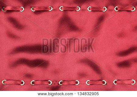 Fashionable beautiful background red satin ribbon inserted in red satin fabric with space for your creativity