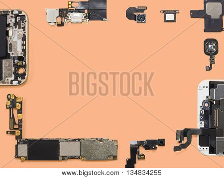 Flat lay (top view) of smart phone components isolate on orange background with copy space