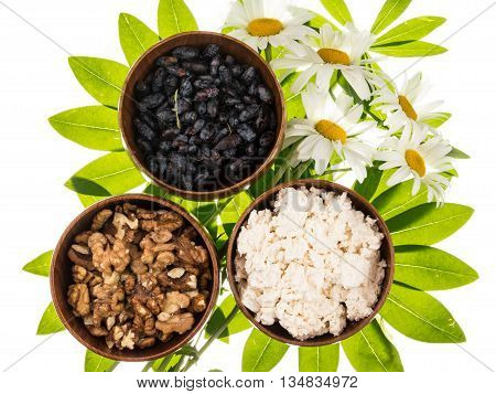 Fresh delicious cottage cheese honeysuckle berries walnuts in brown clay bowl on a background of bright green leaves in the shape of a flower and wild daisies isolated on white background