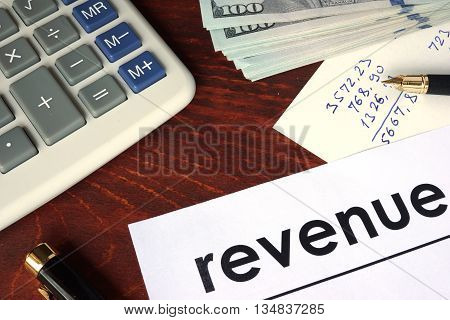 Revenue written on a paper. Financial concept.