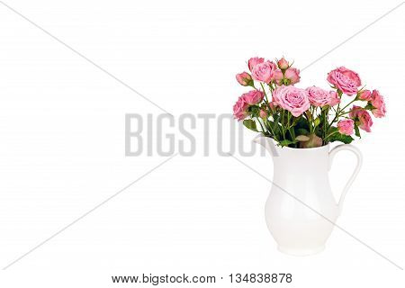 Pink flowers in white jug. Roses in jug. Isolation. Postcard background. Wedding card background. Wedding invitation. Pink roses. Pink roses in a white vase on white background with copy space.