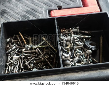 Bolts and screws from metal, lie in a plastic container