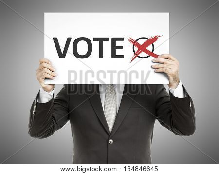 A business man holding a paper in front of his face with the message vote