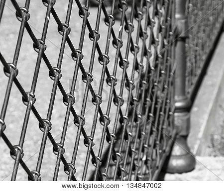 indistinct fragment of an old iron fence closeup in park in outdoor and a blank space of monochrome tone