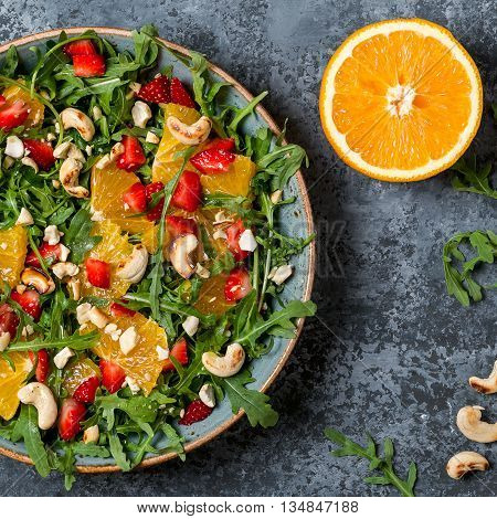 Fresh salad with arugula fruits and nuts. Healthy food.