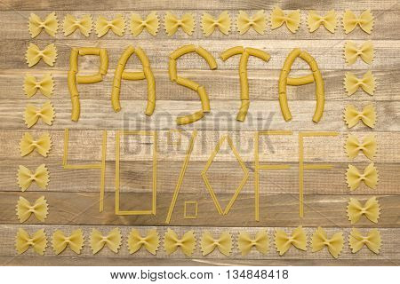 pasta forty percent off text made of raw pasta on wood