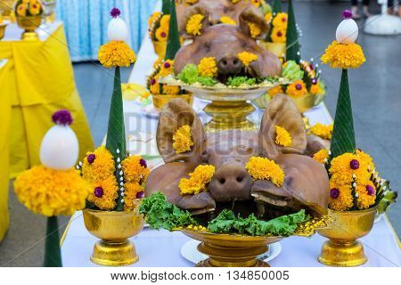 Boiled pig's heads decorated with flowers in ceremony to salute the Bangkok City Pillar ShrineThailand.