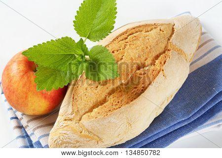 close up of diamond shaped ciabatta bread and fresh apple on striped dishtowel