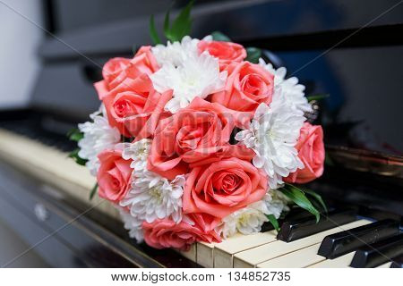 the bride's bouquet on the keys of a piano