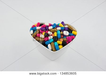 Colorful pills and capsule in a cup on white background