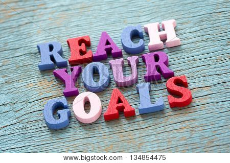 Reach Your Goals Phrase On Vintage Wooden Background