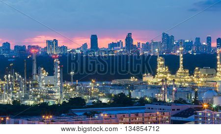 Oil refinery light night with city downtown background after sunset
