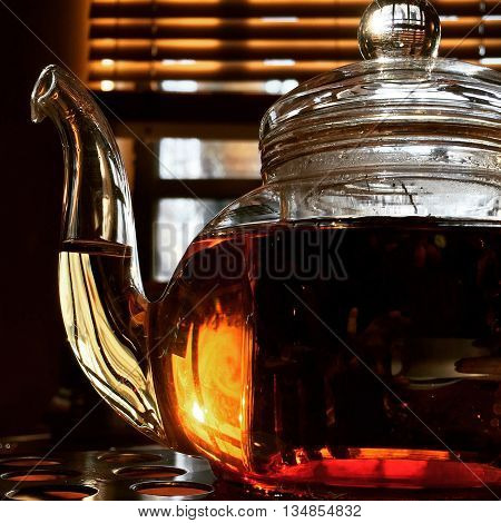 Teapot with black tea, earl grey tea pot, perfect tea color, glass teapot in the light