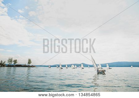 Miass Russia - June 7 2016: group of young athletes on boats of Optimist class sailing on lake during Cup regatta Fyodor Konyukhov