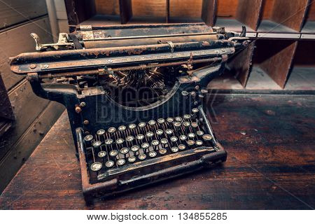 Top view of old typewriter on wooden table. Warm effect and color-toning applied.