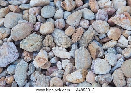 Round sea stones on the beach background and texture