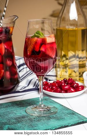 Summer home wine with fruits sangria cocktail in glass and jar fresh dogwood berries on plate
