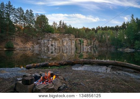 Tourist destination with a bonfire on the shore of the lake career