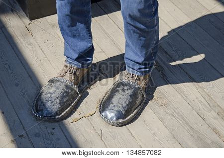Irkutsk region Russia - May10 2015: Iron sculpture home slippers for men on wooden floor