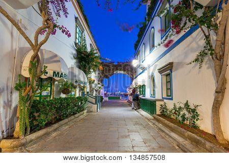 PUERTO DE MOGAN, GRAN CANARIA, SPAIN - APRIL 25, 2016: Pedestrian alley in the harbor area of Puerto de Mogan at night, Gran Canaria in Spain. It's called a Little Venice of the Canaries.