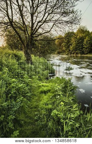 Beautiful Sunrise Landscape Image Of River Flowing And Lush Green Riverbank