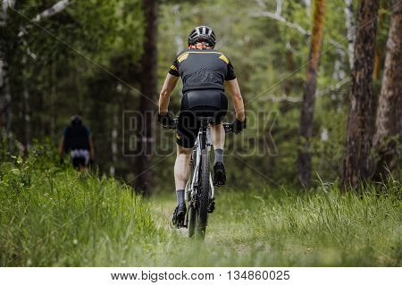 rear view of a male cyclist riding on green grass in forest
