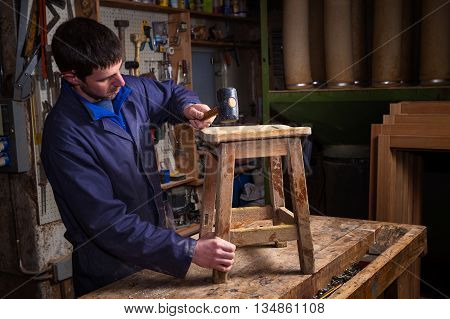 Carpenter Restoring Wooden Stool Furniture In His Workshop.