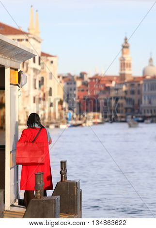 Elegant Woman Dressed In Red With Red Purse Awaits Boat On The Grand Canal In Venice