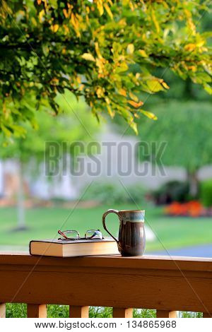 Novel resting on porch railing with a drinking mug on beautiful summer evening just before dusk.