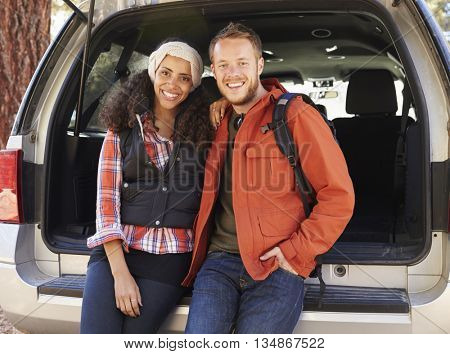 Portrait of mixed race couple sitting in open back of a car