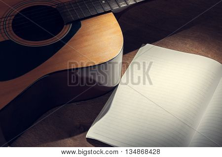 guitar with paper on wood background in vintage style