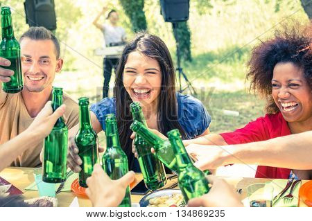 Multiracial friends having fun at barbecue garden party - Friendship concept with young happy people cheering beer bottles at summer picnic - Vintage cross processed filter with focus on middle girl