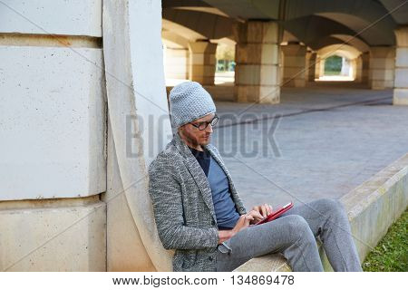 Modern young man with tablet pc touch working under a bridge with wool winter cap