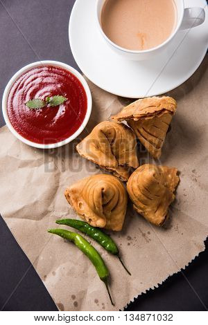 Samosa snack with tomato ketchup and hot tea, Fresh samosas with ketchup and hot chai ready for breakfast