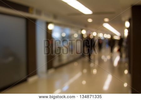 Unfocused people walk through a commercial gallery hall