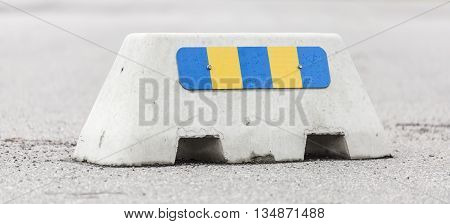 A Jersey Barrier with Retro reflector on asphalt.