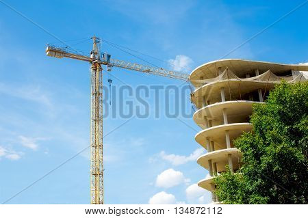 construction crane and unfinished high-rise building. construction of hotel, office building or a shopping mall on a background of blue sky