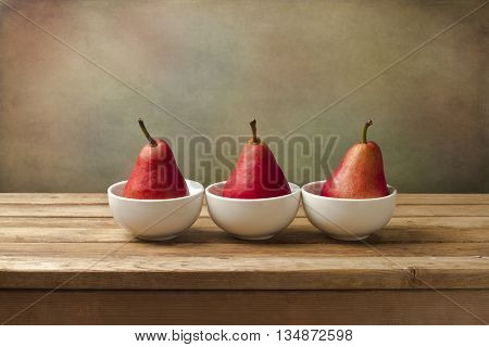 Fine art still life with red pears on wooden table
