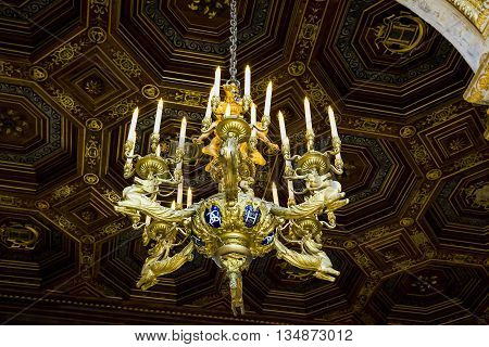 FONTAINBLEAU, FRANCE - MAY 16, 2015: This is one of the chandeliers with the symbol of Napoleon III in ballroom of the castle.