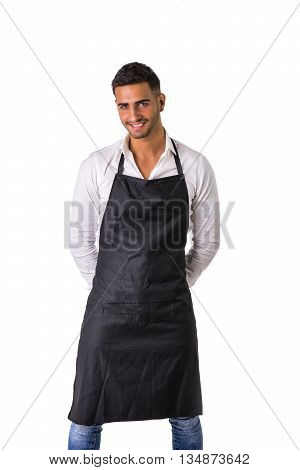 Young chef or waiter posing, welcoming guests with a smile, wearing black apron and white shirt isolated on white background