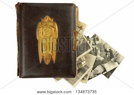 Vintage photo album (circa 1900) with buckle, brass engraved decoration and falling out retro photos (circa 50s) isolated on white