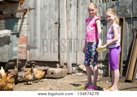 two sisters children fed chickens grain on the farm