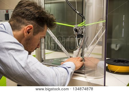 Brunet adult man working with 3D printer, observing the machine at work