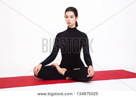 Beautiful athletic girl in black suit doing yoga. Padmasana asana lotus pose. Isolated on white background.