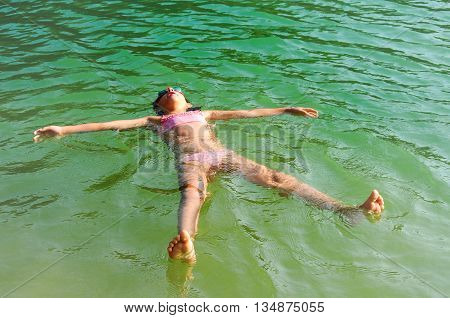 Young girl floats in the lagoon water on vacation
