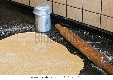 Pizza dough with rolling pin and flour on kitchen table