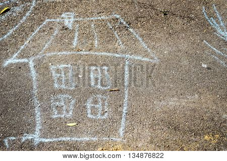 child's drawing with crayons on the pavement: a house with windows and roof and free space for your text