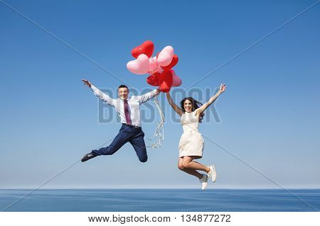 Happy wedding couple jumping over the sea with red air-balloons